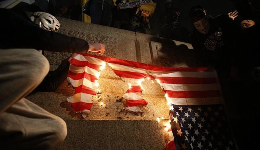 UK anti-govt. protesters march in London, burn US flag
