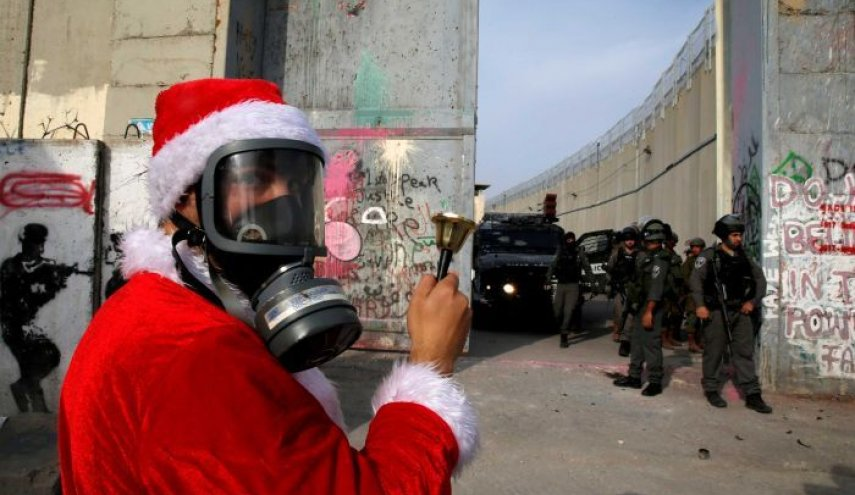 Palestinians dressed as Santa clash with Israeli forces in Bethlehem